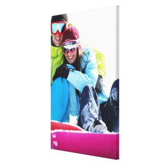 Snowboarder couple sitting on snow canvas print
