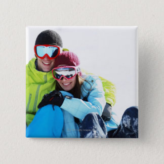 Snowboarder couple sitting on snow pinback button