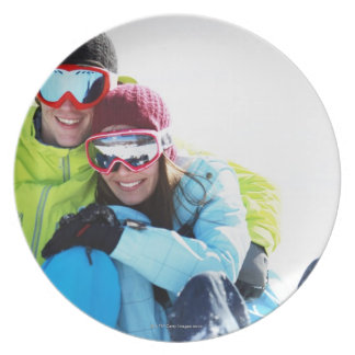 Snowboarder couple sitting on snow plate