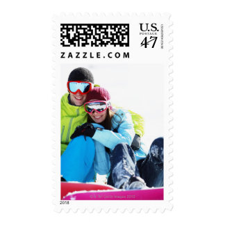 Snowboarder couple sitting on snow postage