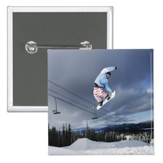 Snowboarder jumping in mid-air doing a backside button