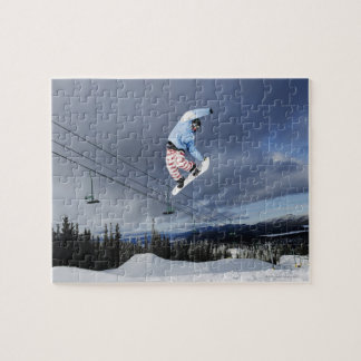 Snowboarder jumping in mid-air doing a backside jigsaw puzzle