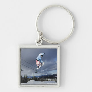 Snowboarder jumping in mid-air doing a backside keychain