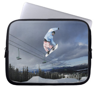 Snowboarder jumping in mid-air doing a backside laptop sleeves