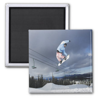 Snowboarder jumping in mid-air doing a backside magnet