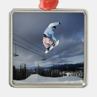 Snowboarder jumping in mid-air doing a backside metal ornament