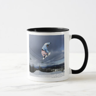 Snowboarder jumping in mid-air doing a backside mug