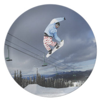Snowboarder jumping in mid-air doing a backside plates