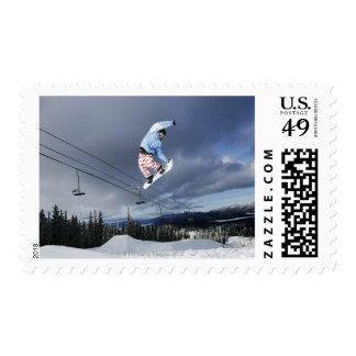 Snowboarder jumping in mid-air doing a backside postage