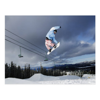 Snowboarder jumping in mid-air doing a backside postcards