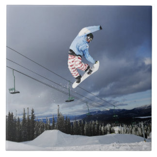 Snowboarder jumping in mid-air doing a backside tile