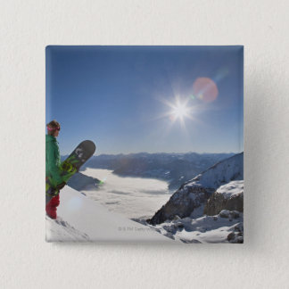 Snowboarder looking from mountain top button
