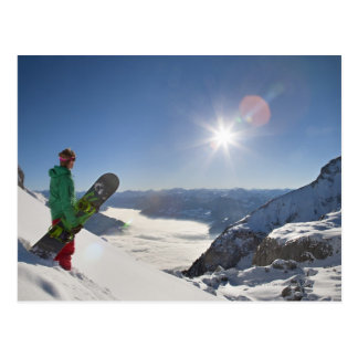 Snowboarder looking from mountain top postcard