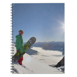 Snowboarder looking from mountain top spiral notebook