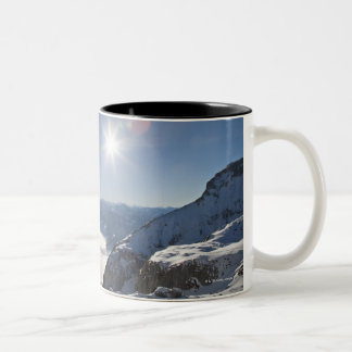 Snowboarder looking from mountain top Two-Tone coffee mug