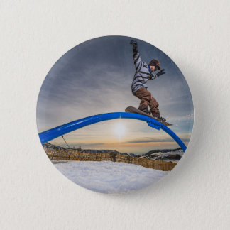 Snowboarder sliding on a rail button