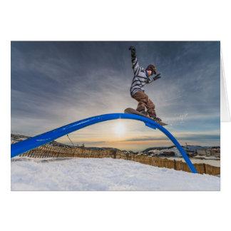 Snowboarder sliding on a rail card
