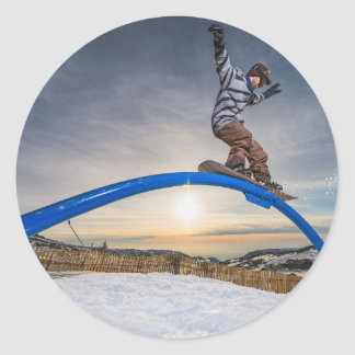 Snowboarder sliding on a rail classic round sticker
