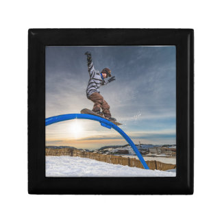 Snowboarder sliding on a rail gift box
