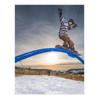 Snowboarder sliding on a rail letterhead