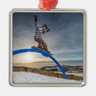 Snowboarder sliding on a rail metal ornament