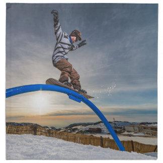 Snowboarder sliding on a rail napkin
