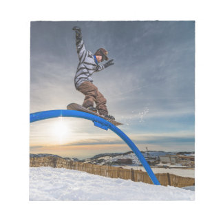 Snowboarder sliding on a rail note pad