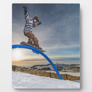 Snowboarder sliding on a rail plaque