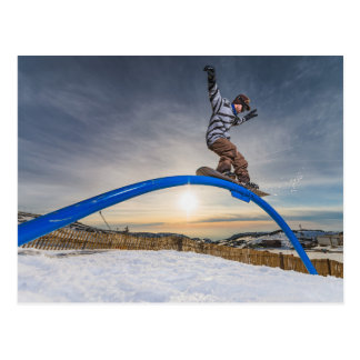 Snowboarder sliding on a rail postcard