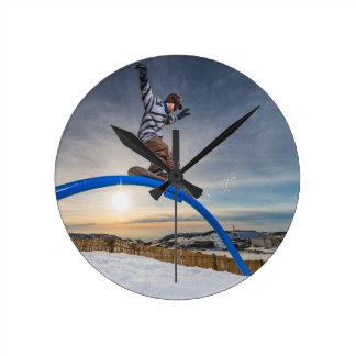 Snowboarder sliding on a rail round clock