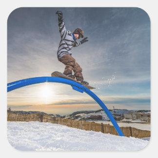 Snowboarder sliding on a rail square sticker