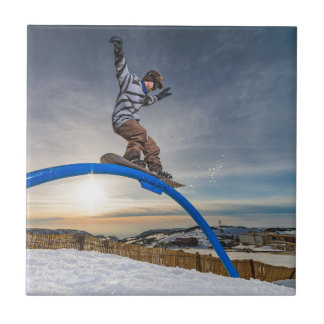 Snowboarder sliding on a rail tile