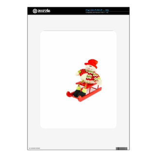 Snowman figurine sitting on red sledge iPad skins
