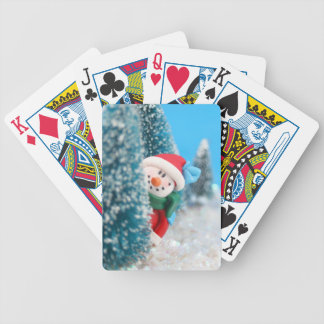Snowman hiding or peeking from behind a tree bicycle playing cards