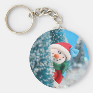 Snowman hiding or peeking from behind a tree basic round button keychain
