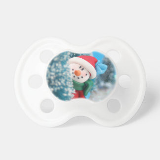 Snowman hiding or peeking from behind a tree pacifier