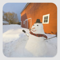 Snowman in front of red barn in Columbia Falls Square Stickers