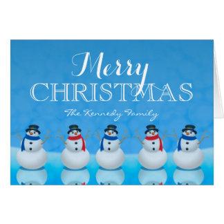 Snowmen in row against blue background card