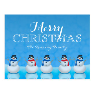 Snowmen in row against blue background postcard