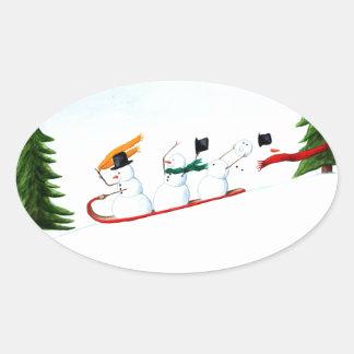 Snowmen on a Sled Oval Sticker