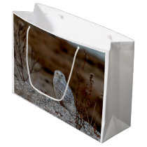 Snowy owl sitting on a rock large gift bag