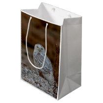 Snowy owl sitting on a rock medium gift bag
