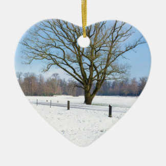 Snowy winter landscape with bare tree and blue sky ceramic ornament
