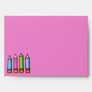 Sobre rosado coloreado de la tarjeta de los lápice