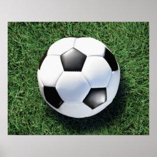 Soccer ball on green grass, close-up poster
