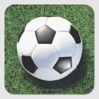 Soccer ball on green grass, close-up square sticker