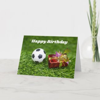 Soccer ball with birthday gift box on green grass card