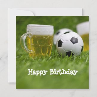 Soccer ball with glass of beer on green grass