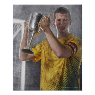 Soccer captain holding up trophy cup on field poster