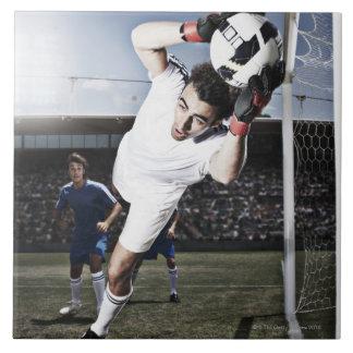 Soccer goalie catching soccer ball ceramic tile
